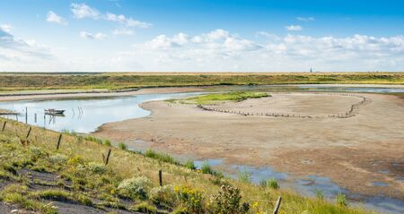 dikes: Colorful Dutch nature reserve with salt water between two dikes on a sunny day in summertime. Stock Photo