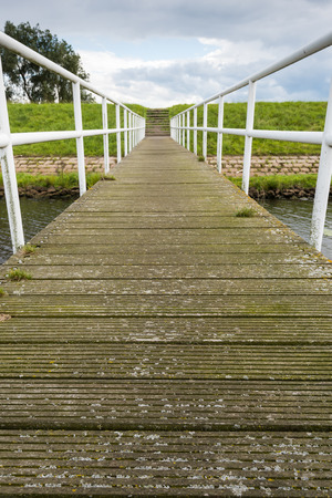 nonslip: Jetty of wooden non-slip shelves and an iron railing. At the end of the jetty a concrete staircase on the embankment. Stock Photo
