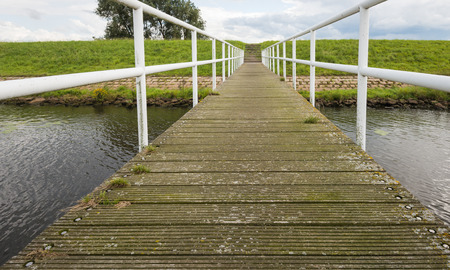 nonslip: Jetty of wooden non-slip shelves and a metal railing. At the end of the jetty a concrete staircase on the dike. Stock Photo
