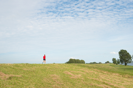 runing: Male runner with a red t-shirt and a black runing trousers runs alone on a Dutch dike on a sunny day in the summer season. Stock Photo