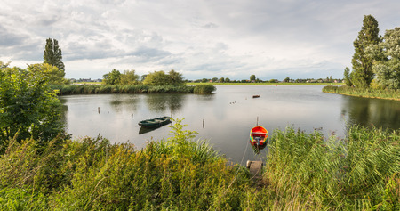 outboard: A small red boat with an outboard motor and a traditional rowboat are both moored at wooden pilings in the water. Its a cloudy day in the summer season.