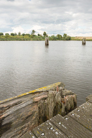 decaying: Decaying part of a wooden pier in a river. Its a heavy clouded day in the summer season. Stock Photo