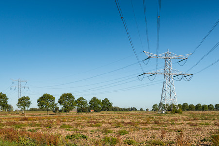 agricultural engineering: High voltage pylons with power lines in een agricultural landscape on a sunny day with a blue sky.
