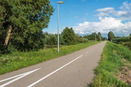 Landelijk landschap met een rechte asfaltweg met bomen en lantaarnpalen aan de kant van de weg. Stockfoto