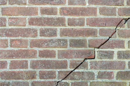 Closeup of a masonry brick wall with a large diagonal crack across the masonry.