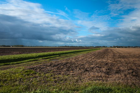 divided: Thereatening dark clouds above an agricultural field after harvest. The landscape is diagonally divided in half by a ditch with grass on the banks.