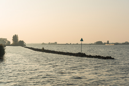 freighter: Backlit picture of a dam with a beacon in a large Dutch river. In the background a sailing freighter. It is evening and the sun is already low. Stock Photo