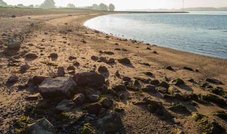 adds: Bank of a wide Dutch river in the early morning from close. The low sun adds a special effect on the stones and the texture of the sand.