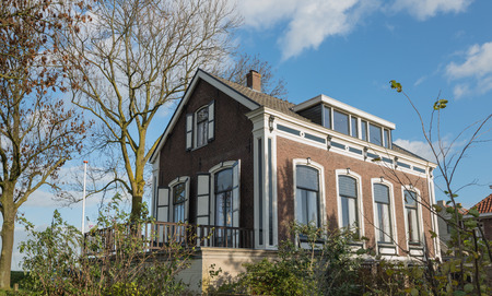 Listed mansion built in 1889 as a doctors residence and still used as such in a small village in the Netherlands. Its a sunny day in the fall season.