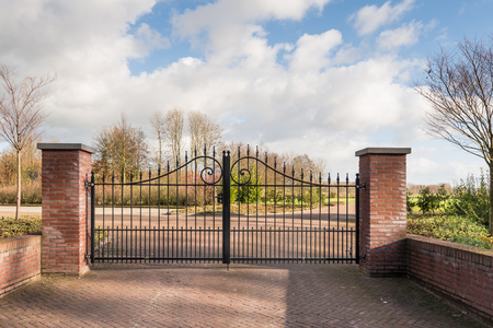 entrance gate: Closed black painted wrought iron gate between two masonry brick pillars at a newly created civilian cemetery. Stock Photo