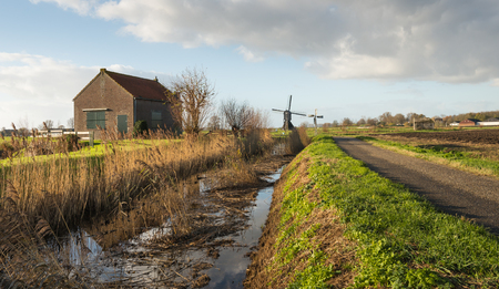 polder: An old pumping station, an historic windmill and a small metallic polder windmill in a polder landscape in the Netherlands. Its early in the morning on a sunny day in the autumn season. Stock Photo