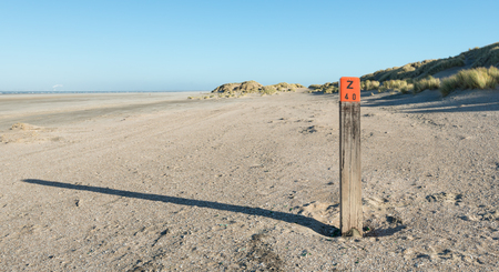 sea mark: Hardwood pole with an orange head and a painted mark on an empty beach at the Dutch North Sea. It is a sunny and windy day in the autumn season.