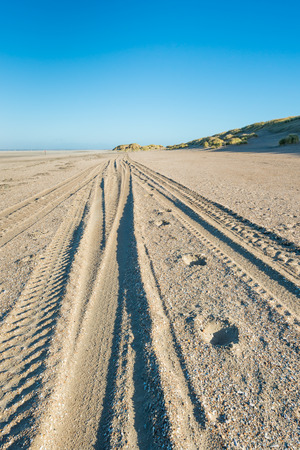 wheel tractor: Converging wheel tracks in the sand of the beach on the Dutch North Sea coast. Its a sunny day in autumn.