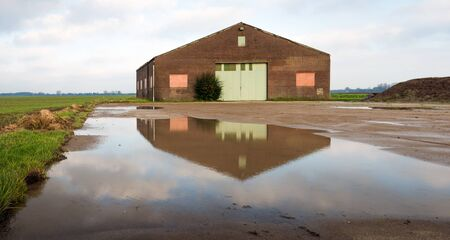 barnyard: Old barn fully reflected in a puddle of water on the barnyard.