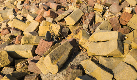 misshapen: Closeup of an overgrown trash heap with the colorful misshapen bricks from a brick factory.
