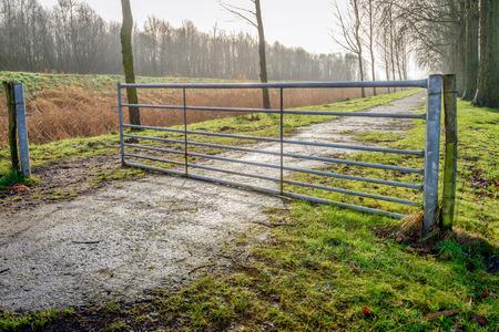 Backlit beeld van een gedeeltelijk geopende gegalvaniseerde ijzeren poort in een landelijk landschap op een zonnige winterdag.