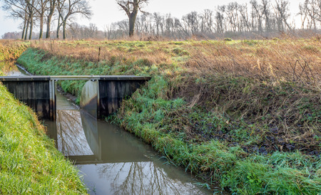 weir: Small weir of wood and steel ditch in a Dutch polder. The light and the mirror-smooth surface cause particular reflections. Stock Photo