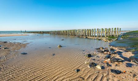 Overzicht van de Nederlandse Noordzee kust met een klein deel van de lange geasfalteerde zeewering. In de zee is een traditionele golfbreker van rijen houten palen. Het is een zonnige dag in de winter.