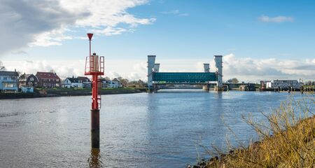 ijssel: Red radar beacon in the foreground and tyhe lifted Algera flood barrier in the river Hollandse IJssel in the background on a sunny day in wintertime.
