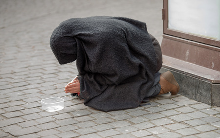 niqab: Woman wearing a black niqab from coarse fabric is praying while she is kneeling on the street with a plastic tray for the collection of money. Stock Photo