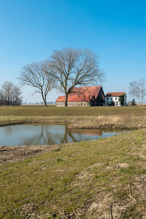 barns winter: White farmhouse and two large barns built in 1874. The buildings are situated in a large Dutch nature reserve. Its a sunny day in the winter season. Editorial