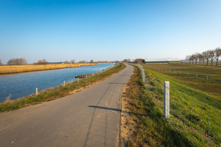 end of a long day: Long asphalt country road along a small river. It is a sunny day in the end of the winter season in the Netherlands.