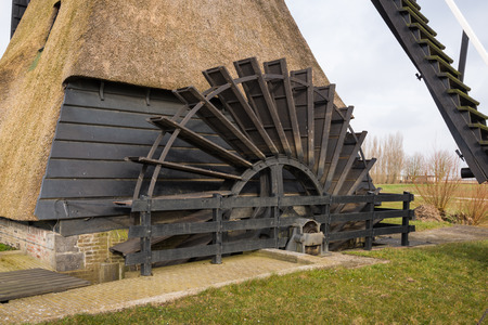 waterwheel: Closeup of the water wheel of a large Dutch wooden hollow post mill. The mill, a national monument, was originally built in 1795 and later partly burnt down and completely restored.