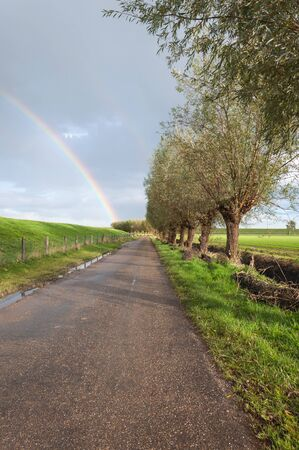 Country road with puddles of rain. In the overcast sky is a true rainbow visible. Stock Photo