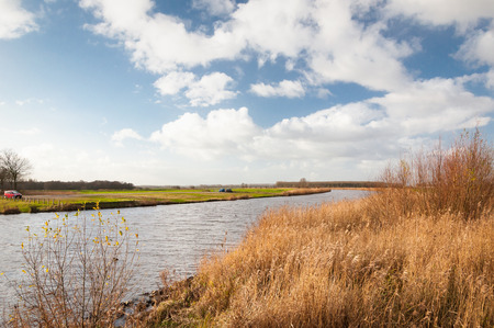 meanders: A small river meanders through the country. The grass and reeds on the edge is yellow and dry.