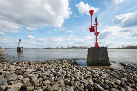 beacons: Colorful radar beacons in the Dutch river Waal on a sunny day in the early spring season. Stock Photo