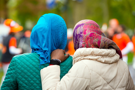 Two black female refugees in the Netherlands seen from the back. Both women wear a colorful scarf. Stock Photo