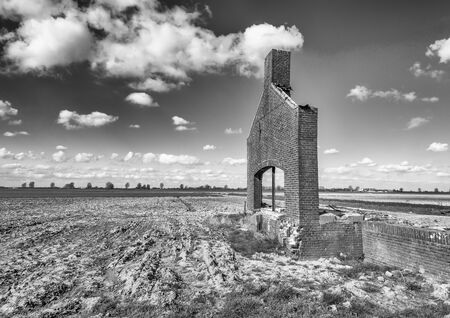 partially: Monochrome image of a partially demolished brick building in a rural Dutch polder area.