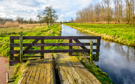 Rural landscape in the Netherlands with a simple bridge and a small stream. Its a sunny day in autumn but the clouds are coming.