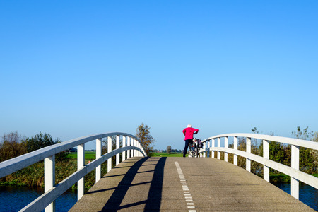 wooden railings: Mature woman with her bike on a narrow bicycle bridge with curved white wooden railings. It is a sunny day in the autumn season in the Netherlands.