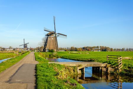 polder: Bright and colorful image of a polder landscape with two wind mills in the Netherlands on a sunny day in the fall season.