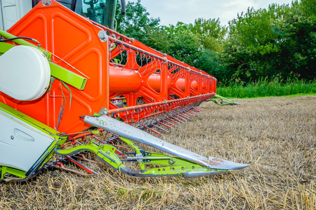 thresh: Closeup of a colorful combine parked at the edge of the field after finishing the work. It is a cloudy day in the middle of summer season. Stock Photo