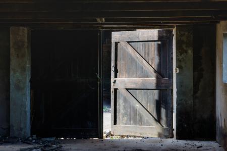 老朽化した納屋のドアを開けて。納屋の中は暗いとそれ以外は晴れた夏の日。