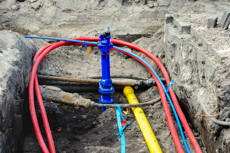 Connecting colorful underground cables and mains at a housing project in the Netherlands.