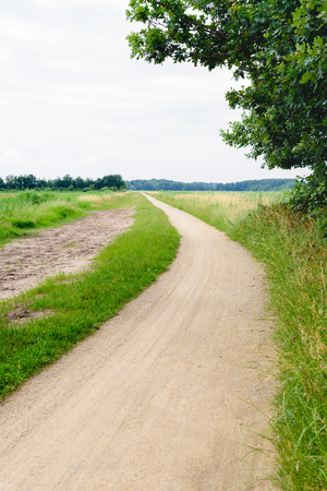 Meandering gritty cycling and hiking trail in a rural area. It is a slightly cloudy day at the beginning of the summer in the Netherlands. Stock Photo