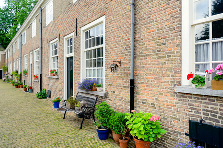 brick facades: Row of historic houses with masonry brick facades in the Begijnhof in the Dutch city of Breda. This beguinage is the oldest beguinage in the Netherlands. Stock Photo