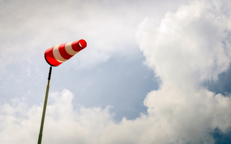 erect: Erect windsock with red and white stripes on a tall post and against a menacing and darkening sky. Bad weather is coming now.