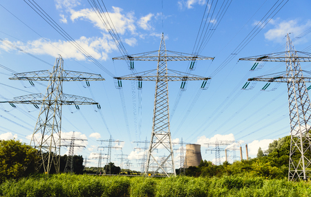 voltages: High voltages lines and riveted steel power pylons in a Dutch landscape. In the background are a concrete cooling tower and some smoking chimneys. Its a sunny summer day.