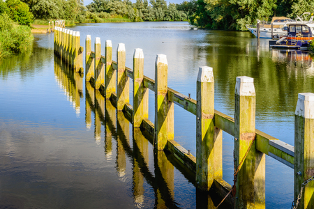 Wooden bollards with a white top in a line at the entrance of a small lock. It is a sunny day at the beginning of the summer season and the poles are reflected in the water surface.