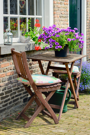 breda: Two small wooden chairs and a table before a historic facade in the Begijnhof in the Dutch city of Breda.
