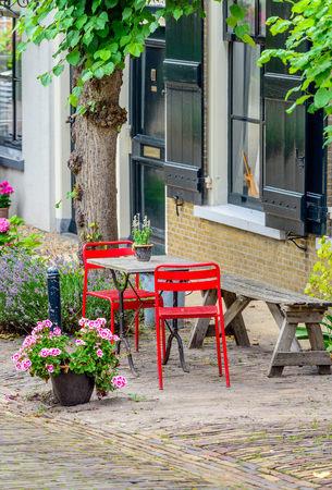 Simple bright red chairs with a small table and an old wooden bench next to a historic Dutch facade.