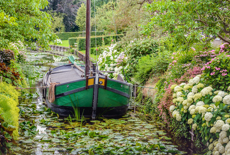 drimmelen: Historic restored ship in the narrow canal of the small Dutch village of Drimmelen. Its summer and many shrubs and plants are in full bloom.