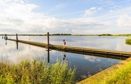 diagonally: Long wooden jetty in a lake with a mirror smooth water surface and diagonally into the image. It is early in the morning on a beautiful, windless summer day.