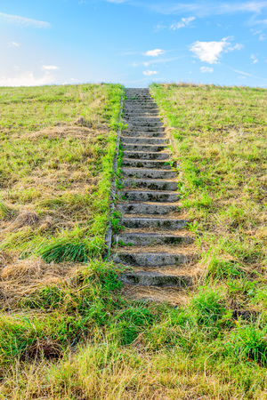 yellowed: Concrete stairs to the top of a dike in the Netherlands. On the steps is yellowed grass. Its a sunny day in the summer season.