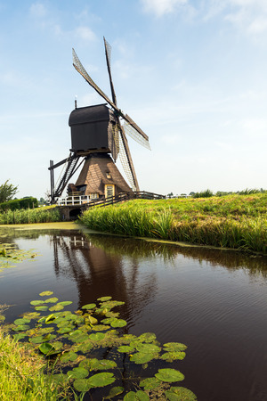 paddle wheel: Wooden hollow post mill with a thatched under tower and a paddle wheel near the village of Molenaarsgraaf, Alblasserwaard, South Holland, Netherlands. The now restored mill dates from about 1655 and is now a protected national monument. Stock Photo