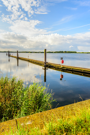 windless: Long wooden jetty in a Dutch lake with a mirror smooth water surface and diagonally into the image. It is early in the morning on a beautiful, windless summer day. Stock Photo